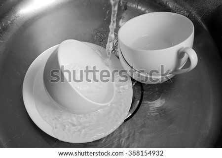 Cups in kitchen sink closeup - stock photo