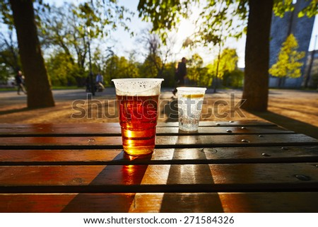 Cups of beer and water in the garden restaurant - stock photo