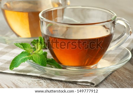 Cups of black and green tea with mint close-up on napkin. - stock photo