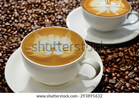 Cups of coffee latte on coffee beans background - stock photo