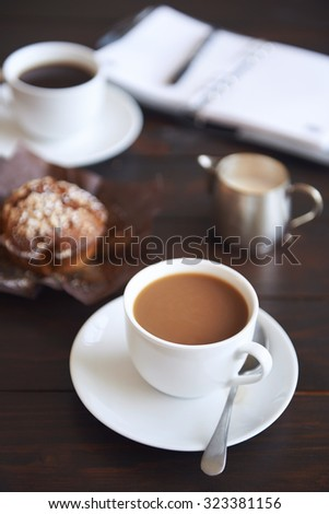 Cups of coffee with a muffin and a daily planner in the background - stock photo