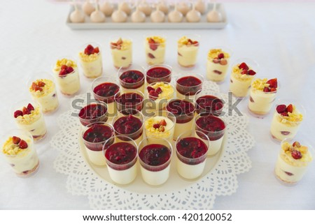 cups of custard sauce with wild berries - stock photo