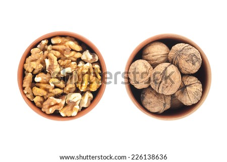 Cups of peeled and unpeeled walnuts. Isolated on white background, top view. - stock photo