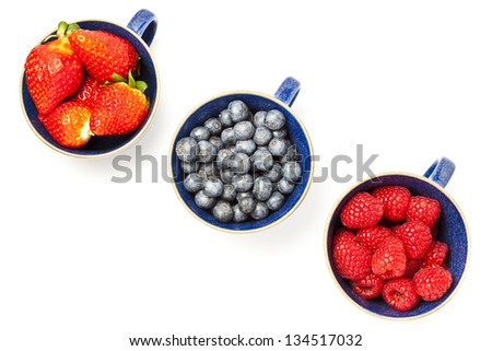 Cups of strawberries, blueberries and raspberries on white background