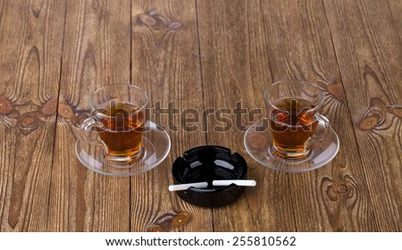 Cups of tea with dishes and black ashtray with cigarettes isolated on the brown wooden texture