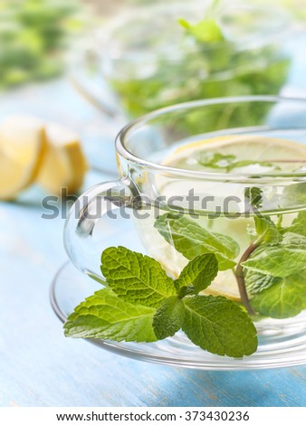 cups of tea with fresh mint and lemon slices on a blue wooden background outdoors - stock photo