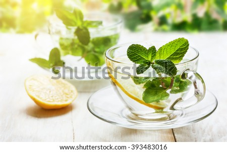 cups of tea with fresh mint and lemon slices on  wooden background outdoors - stock photo