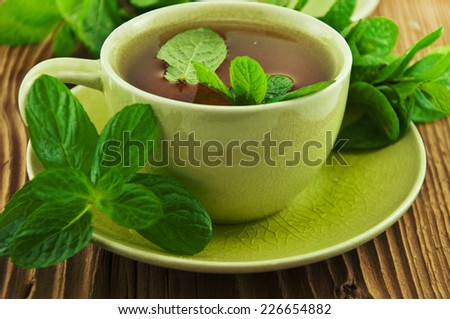 Cups of tea with mint on wooden table. - stock photo