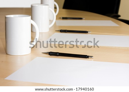 cups pencils and white paper in a meeting room - stock photo