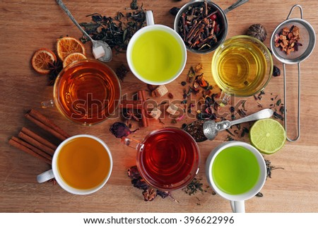 Cups with different kinds of tea and ingredients on table