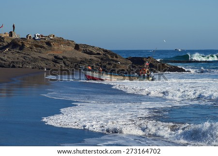 CURANIPE, CHILE - APRIL 22, 2015: Fishing boat coming ashore on the sandy beach in the fishing village of Curanipe, Chile. Once beached on the sand, a tractor pulls the boat to safer ground. - stock photo