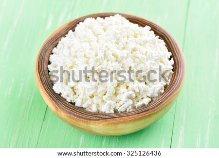 Curd cheese in bowl on green wooden table - stock photo