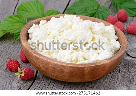 Curd cheese in wooden bowl on rustic table, close up view - stock photo
