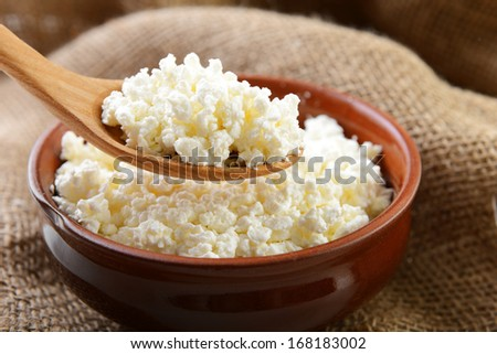 curd in brown bowl on sacking - stock photo