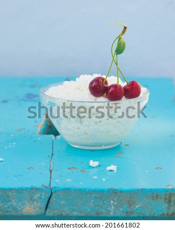 curd with three cherry on blue wooden board  - stock photo