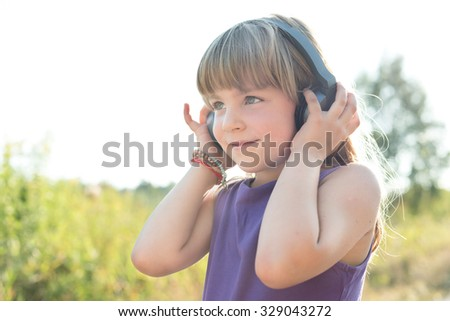 Cure five years old girl smiling and listening to music using black headphones