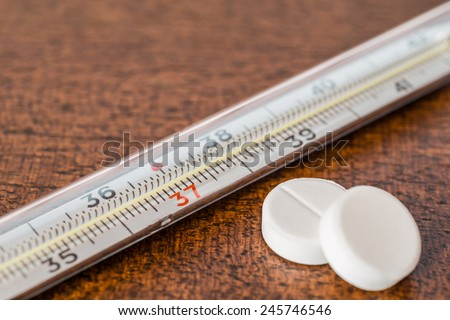 Cure the disease, measure temperature by thermometer and take the pills. Angle view