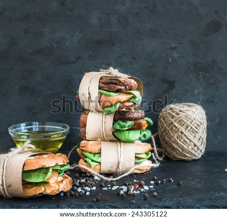 Cured chicken and spinach whole grain sandwich tower with spices and black stone background. Selective focus - stock photo