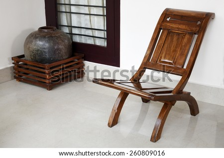 Curios - an antique chair and a large black pot. Geometric lines and shapes. - stock photo