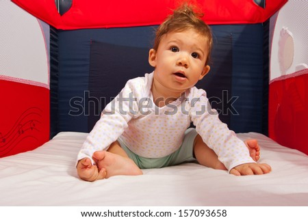 Curious baby boy sitting inside a playpen