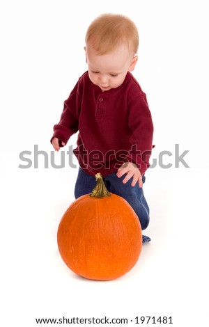 Curious baby boy standing over and looking down on a pumpkin. He wonders, what is the thing?