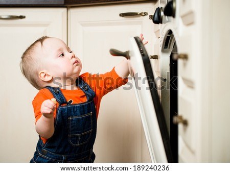 Curious baby watching through glass of kitchen oven - stock photo