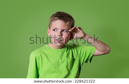 Curious boy listens. Closeup portrait child hearing something, parents talk, gossips, hand to ear gesture isolated on green background. Human face expression, emotion, body language, life perception.  - stock photo