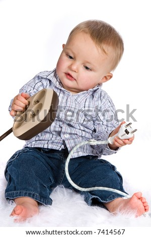 Curious boy playing with plugs and outlets