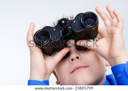 Curious boy with eyeglasses looking through binoculars