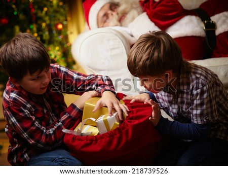 Curious boys choosing gifts from big red sack with Santa Claus sleeping on background - stock photo