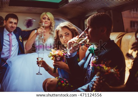 Curious bridesmaid looks at a groomsman drinking champagne