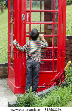 Curious child peeking in a red telephone box - stock photo