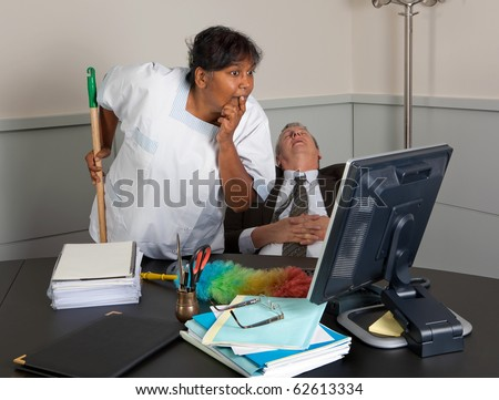 Curious cleaning woman reading the computer while the office manager is sleeping - stock photo