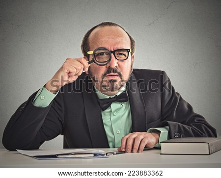 Curious corporate businessman skeptically looking at you through magnifying glass sitting at desk isolated on office grey wall background. Human face expression, body language, attitude, body language - stock photo