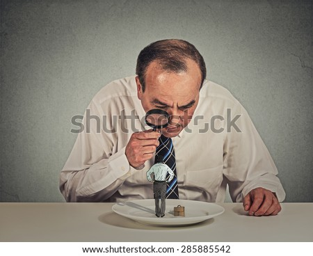 Curious corporate businessman skeptically meeting looking at small employee standing on table plate through magnifying glass isolated grey wall background. Human face expression, attitude, perception