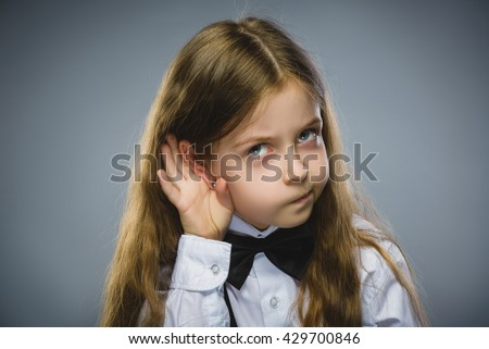 Curious Disappointed girl listens. Closeup portrait child hearing something, parents talk, hand to ear gesture isolated grey background. Human face expression, emotion, body language, life perception - stock photo