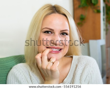 Curious european blonde sitting on sofa at domestic interior