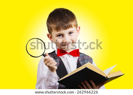Curious Exploring little boy with magnifying glass holding a book on yellow background. - stock photo