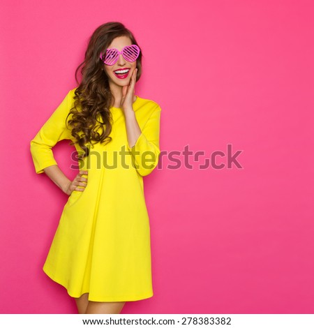 Curious Girl In Pink Sunglasses. Smiling beautiful girl in pink sunglasses and yellow mini dress holding hand on chin and looking away. Three quarter length studio shot on pink background. - stock photo