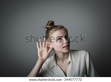 Curious girl in white is eager to know all the gossip. Young slim woman. - stock photo
