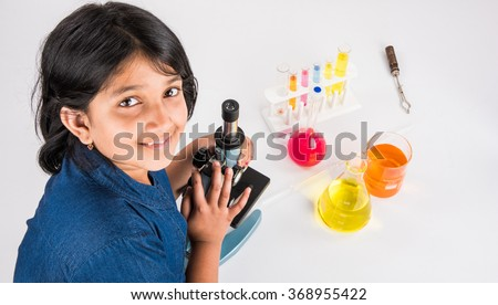 curious indian girl with microscope, asian girl with microscope, Cute little girl holding microscope, 10 year old indian girl and science experiment, girl doing science experiments, science lab - stock photo