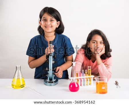 curious indian girls with microscope, asian girls with microscope, Cute little girls holding microscope, 10 year old indian girls and science experiment, girls doing science experiments, science lab - stock photo