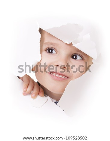 Curious kid looks up through a hole in white paper - stock photo