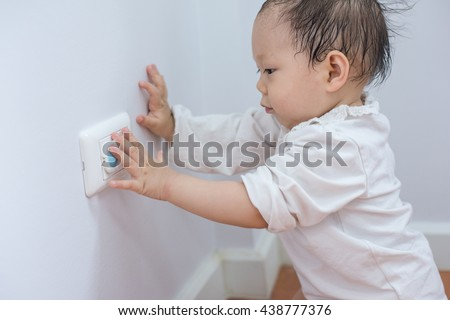 Curious Little Boy Playing With Electric Plug. Trying To Insert It Into The  Electric Socket