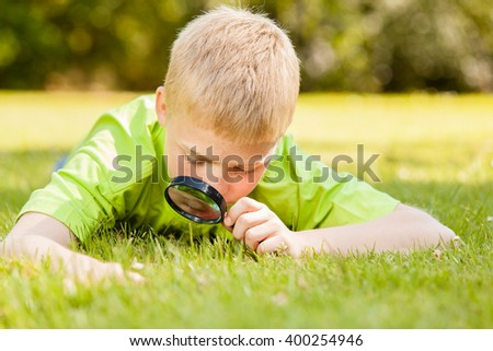 Curious male child in blond hair and green shirt laying down on grass while looking at something through a black magnifying glass outdoors - stock photo