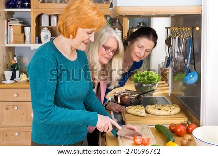 Curious Middle Age Moms Looking at their Smiling Friend Slicing Ingredients for their Dinner Recipe. - stock photo