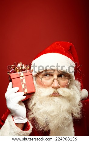 Curious Santa Claus holding red package by his ear - stock photo
