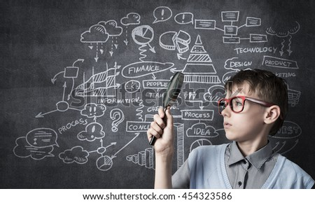 Curious school boy with magnifier