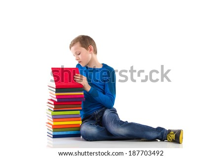 Curious schoolboy. Schoolboy sitting on the floor and reading a book. Full length studio shot isolated on white. - stock photo
