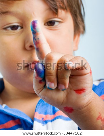 Curious Three year old Child is looking at his painted finger. Closeup portrait on white background - stock photo